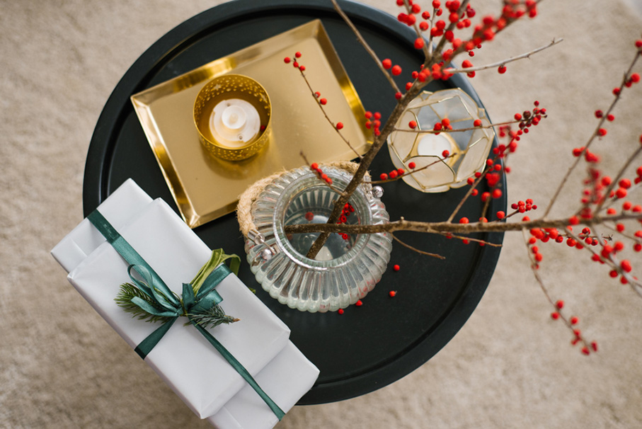 Gift boxes tied with emerald ribbon on a black coffee table