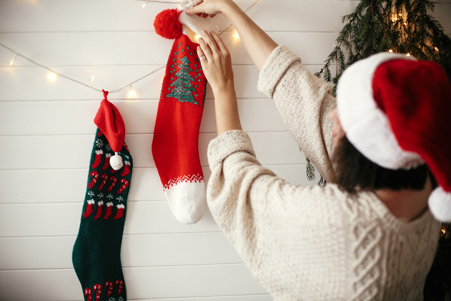 Stylish girl in cozy sweater and santa hat decorating room for christmas holidays
